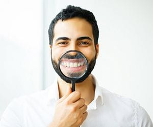 man holding magnifying glass to his smile with dental crowns in Hillsboro