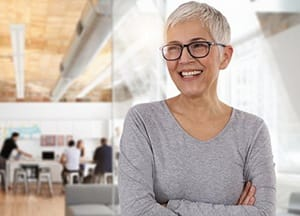 happy older woman standing with her arms crossed in an office