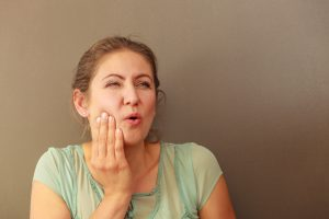 woman holding face painfully from toothache